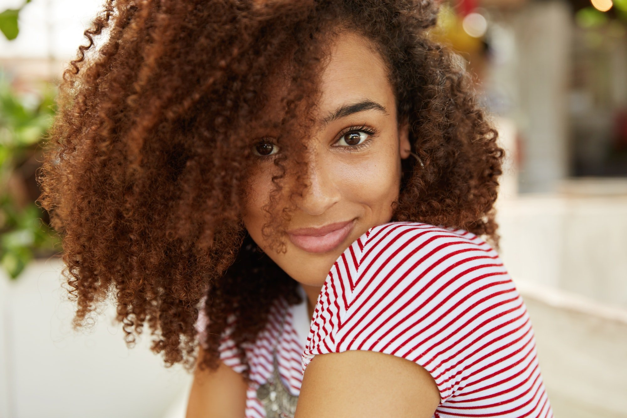 Sideways portrait of stylish female with curly Afro hairstyle and dark skin, being satisfied to achi